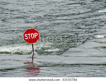 Stop sign in flooded river - stock photo