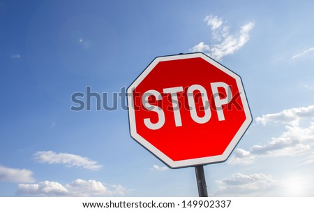 stop sign in front of a cloudy summer sky