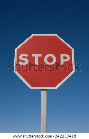 Stop sign isolated over blue sky - stock photo