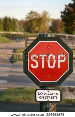 Stop sign near golf course, extra warning about alcohol