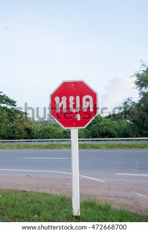 Stop sign on a street background,Thailand Language.