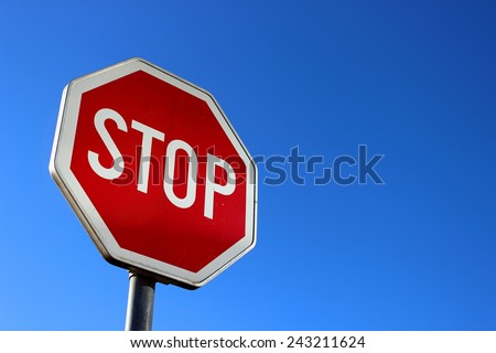Stop sign on blue sky - stock photo