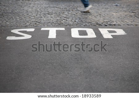 Stop sign on road with man running - stock photo