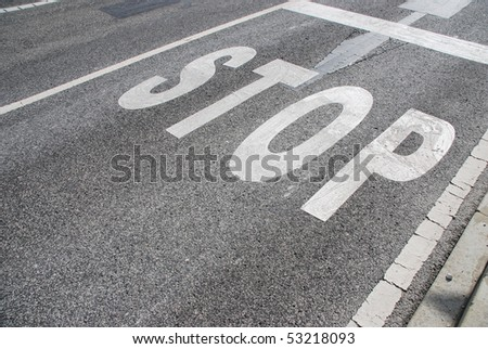 stop sign painted on a asphalt road surface - stock photo