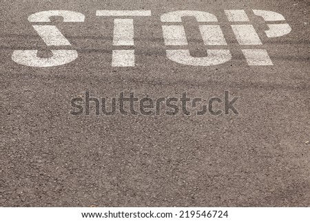 stop sign painted on asphalt