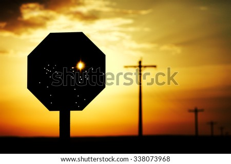 Stop sign that has been riddled with bullet holes against a brilliant morning sun. - stock photo