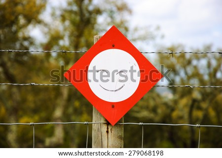 Stop sign with smile attached to barbed wire fence. Never stop smiling / Be positive concepts. - stock photo