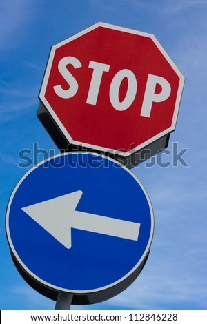 Stop signal with left arrow in blue sky