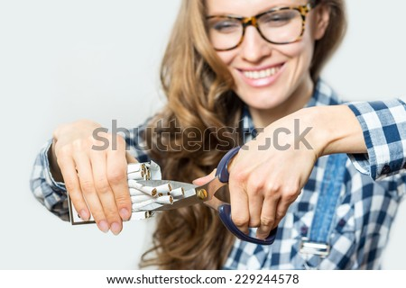 Stop smoking concept. Young woman cut cigarettes with scissors happy smiling. focus on hand, scissors and cigarettes - stock photo