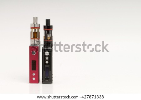 Stop smoking, start vaping. A red and black vape or electronic cigarette placed on the left side on a shaded white background.. Room for text on the right side. - stock photo