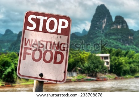 Stop Wasting Food sign with a forest background - stock photo