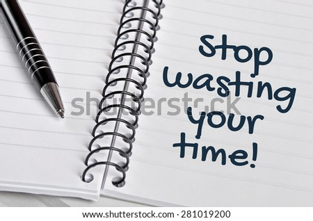 Stop wasting your time word on notebook page - stock photo