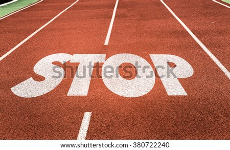 Stop written on running track - stock photo