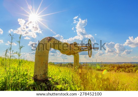 Stopcock on the pipe among grass beneath cloudy sky with sun - stock photo