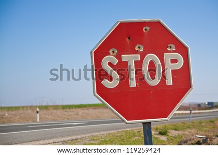 Stopsign with bullet holes - stock photo