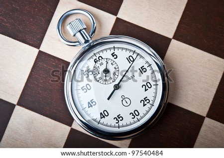 stopwatch and chessboard on a background - stock photo