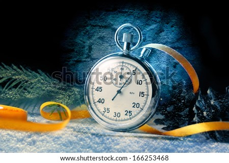 Stopwatch and christmas decoration on black - stock photo