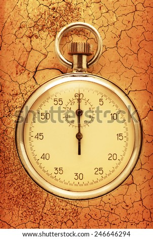 Stopwatch closeup on the cracked brown background - stock photo