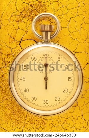 Stopwatch closeup on the cracked yellow background - stock photo