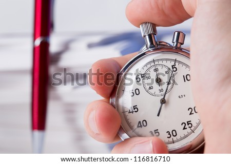 Stopwatch in hand on background of paper cards - stock photo