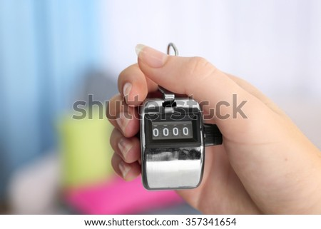 Stopwatch in hand on blurred background, close up - stock photo