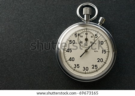 Stopwatch isolated on dark - stock photo