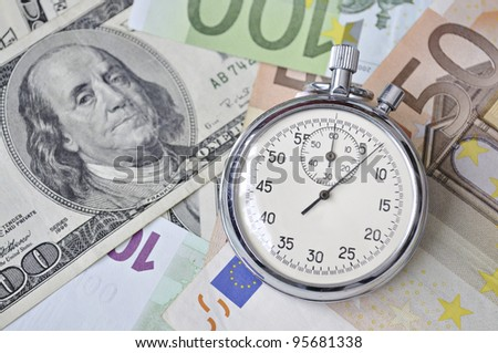 stopwatch lay over Euro and US dollar banknotes; focus on watch - stock photo
