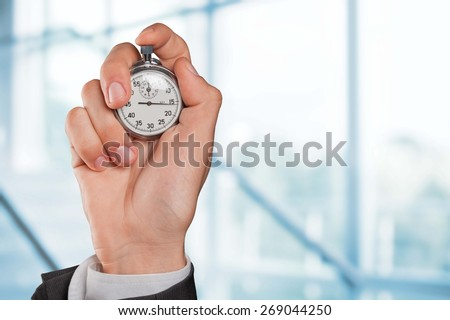Stopwatch. Man's hand holding stopwatch. - stock photo