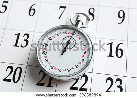 Stopwatch on calendar background, close up - stock photo