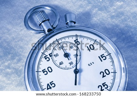 Stopwatch on snow in blue toning - stock photo