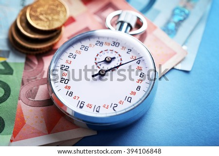 Stopwatch with euro banknotes and coins on blue background. Time is money concept - stock photo