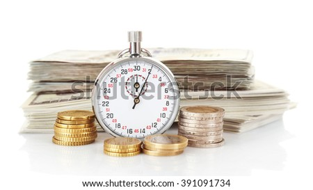 Stopwatch with stack of dollar banknotes and coins, isolated on white. Time is money concept - stock photo