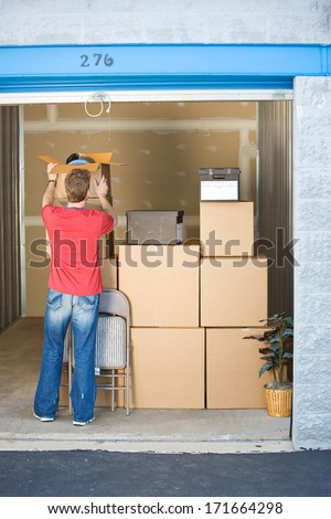 Storage: Man Stacking Boxes and Things In Storage - stock photo