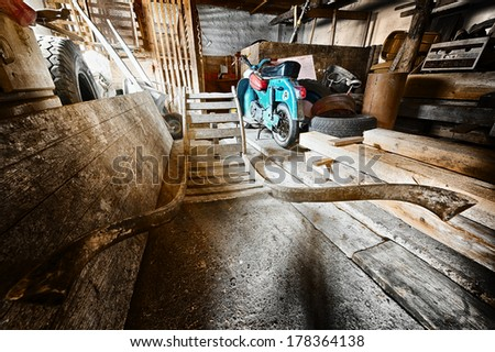 storage room in old barn with old moped and wooden barrow - stock photo