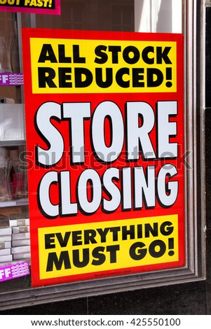 Store closing poster in a window of a bankrupt shop advertising all stock reduced - stock photo