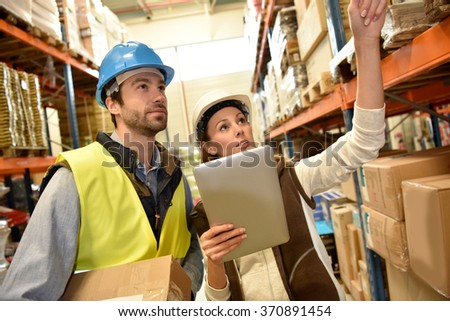 Store manager with warehouseman checking stock levels - stock photo