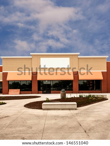 Storefront with awning ready for new tenant at a mixed use retail strip mall - vertical - stock photo