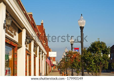 Storefronts, sidewalks, and lamp posts in small-town America - stock photo