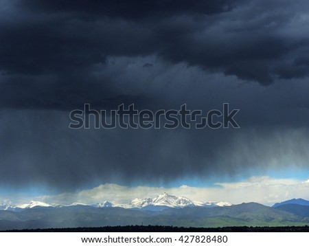 Storm approaches Broomfield, Colorado, over the Rocky Mountains, with long's peak still in sunlight - stock photo