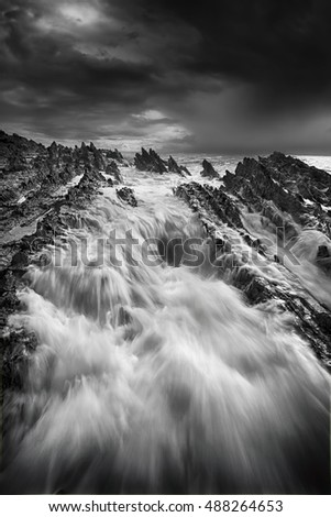 Storm approaching and rough seas with big flows over jagged deathly rocks
