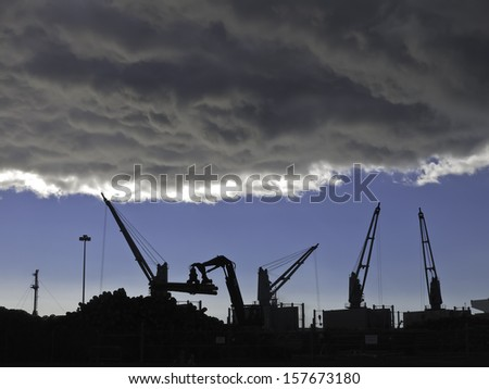 Storm cloud over silhouettes of cranes lifting logs to be shipped from seaport of Astoria, Oregon - stock photo