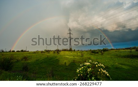 storm clouds and rain rainbow power line, spring landscape