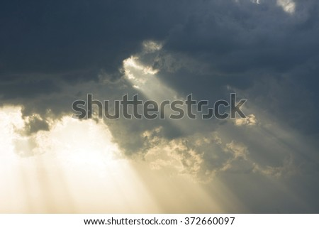 Storm clouds background with sun beams passing through - concept of hope