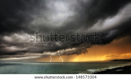 Storm clouds coming over sea with lightning and thunder clouds - dramatic ocean seascape / nature landscape of thunder storm. - stock photo