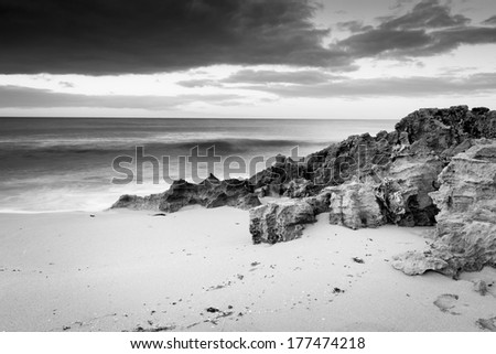 Storm clouds creep in over the ocean with rocks and sand in black and white - stock photo