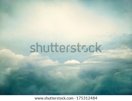 Storm clouds done with yellow and green retro colors.  Image displays a pleasing paper grain and texture at 100 percent.  - stock photo
