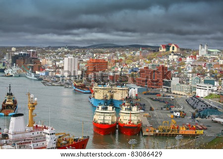 Storm clouds form over the city of St. John's and St. John's busy harbour. - stock photo