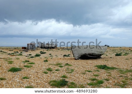 Storm clouds gather over the beach at Dungeness, Kent, with abandoned buildings and boats.