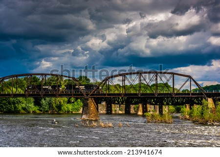 Storm clouds over a train bridge and the Delaware River in Easton, Pennsylvania. - stock photo