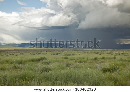 Storm clouds over grasslands and mountains at Red Rock Lake in Centennial Valley, near Lakeview, Montana - stock photo